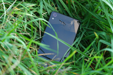 Broken phone is in grass.
