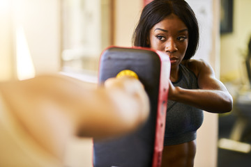 african american woman tolding target pad for boxing training