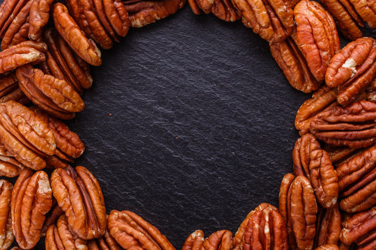 delicious pecan nuts on a dark stone background