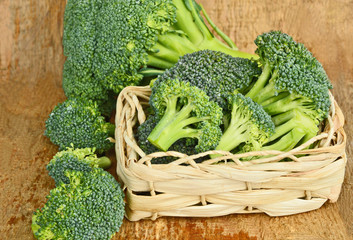 healthy and benefits of Broccoli. .a lot of broccoli in basket on wooden background.