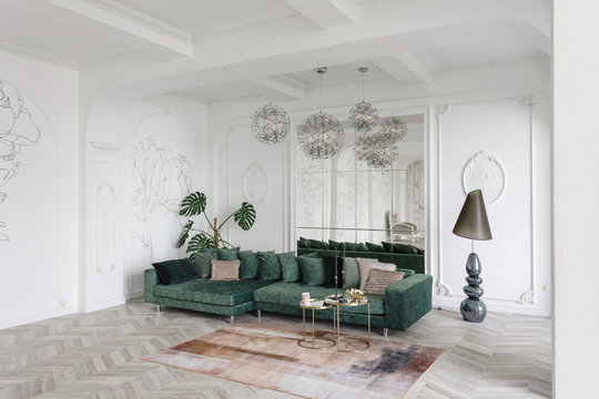 Morning in luxurious light interior in hotel. Bright and clean interior design of a luxury living room with parquet wood floors, fireplace, sofa and houseplant. Stucco on walls