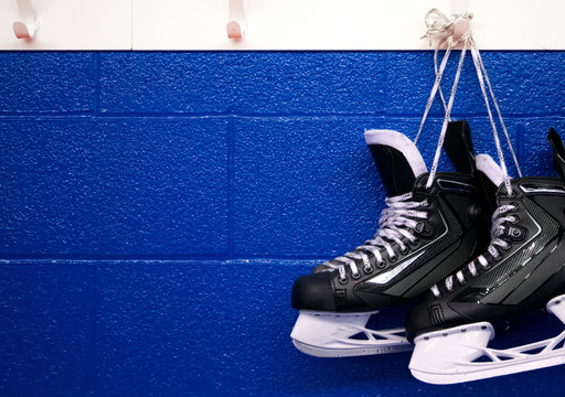 Hockey skates hanging over blue wall with copy space