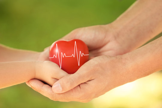 Adult and child hands holding heart on blurred background, closeup. Family concept
