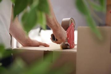 Man packing carton box indoors, closeup. Moving day