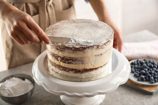 Woman decorating delicious cake with fresh cream on stand. Homemade pastry
