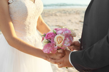 Close up view of wedding couple holding bouquet on beach
