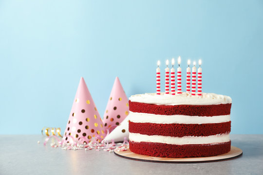Delicious homemade red velvet cake with candles on table against color background. Space for text