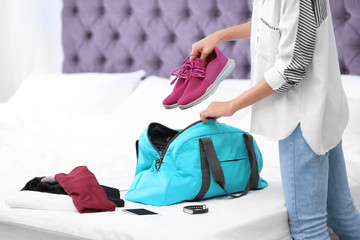 Young woman packing sports stuff for training into bag in bedroom