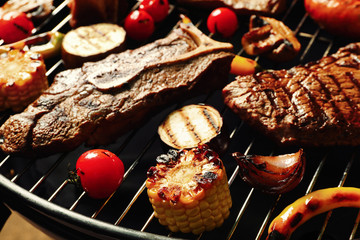 Fresh grilled meat steaks and vegetables on barbecue grate, closeup