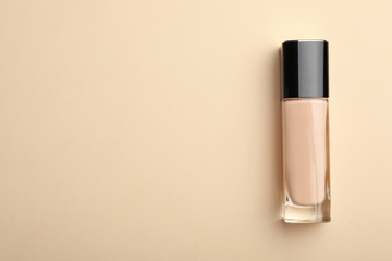 Bottle of skin foundation and space for text on color background, top view