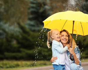 Happy mother and daughter with umbrella under rain in park. Space for text