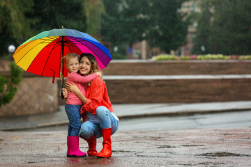 Wall Mural - Happy mother and daughter with bright umbrella under rain outdoors