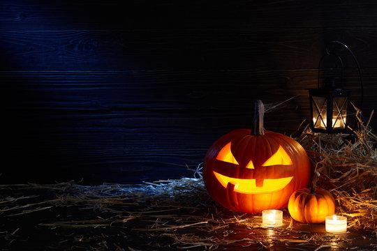 Carved pumpkin or jack-o-lantern in dark barn, Halloween holiday celebration concept