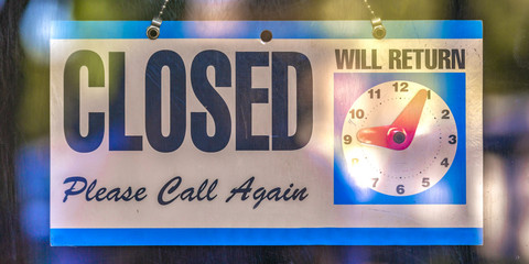Closed sign with clock icon on a glass door