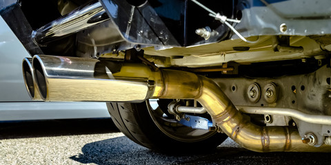 Dual chrome exhaust pipe at the bottom of a car