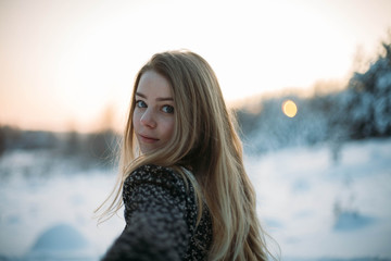 blonde girl in a snow forest in winter.