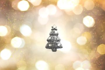 キラキラなゴールドと黒のボケ背景の真ん中に黒いクリスマスツリーの輪郭
