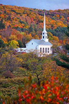 A church surrounded by fall foliage in Stowe, Vermont