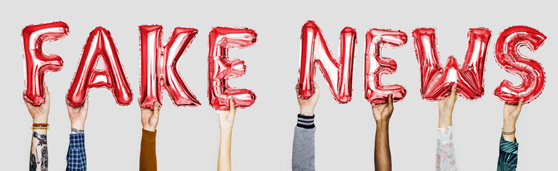 Red alphabet helium balloons forming the text fake news