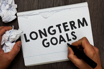 Writing note showing Longterm Goals. Business photo showcasing Strategic target that is required more time for completion Man holding marker notebook crumpled papers several tries made
