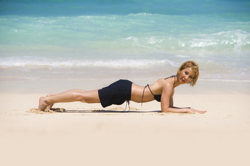 isolated portrait of young happy and beautiful sporty and fit woman doing plank exercise on beach sand smiling cheerful in wellness fitness and healthy lifestyle concept