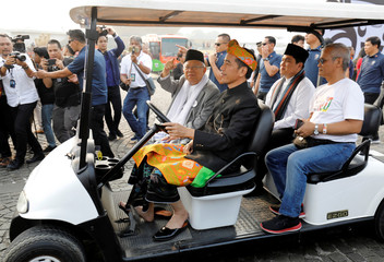 Indonesian President Joko Widodo and his running mate Ma'ruf Amin ride in a cart during a parade at a ceremony marking the start of the campaigning period for next year's presidential election in Jakarta