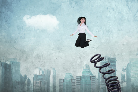 Female entrepreneur jumps by using a big spring