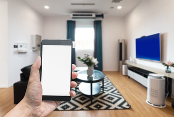 Man hands holding blank screen a smartphone and blurred living room background.