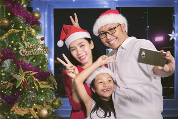 Parents and child take photo at Christmas time