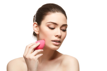 girl with makeup sponge isolated on white