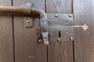 Portone in legno con chiavistello a scorrimento in ferro, catenaccio chiuso