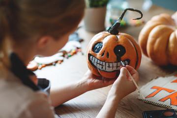 woman artist prepares for halloween and paints pumpkins