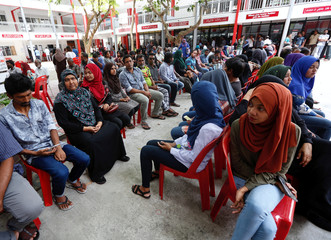 Peolple sit in line as they wait to cast their votes at a polling station during the presidential election in Male