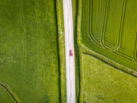 Aerial view looking down on a rural road in the UK countryside with a car racing along it. On a bright sunny day, farmland and crops can be seen either side of the road