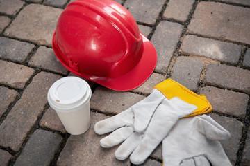 red helmet, coffee mug and work gloves