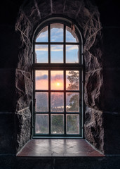 Cosy view looking through an old window with sunset at autumn morning in National Park, Finland