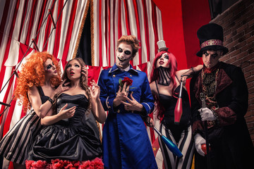 Circus troupe from freak show staying on stage of daark circus