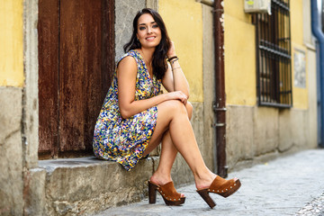 Happy young woman with blue eyes smiling sitting on urban step.