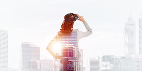 Woman in mask against sunrise above city trying virtual reality