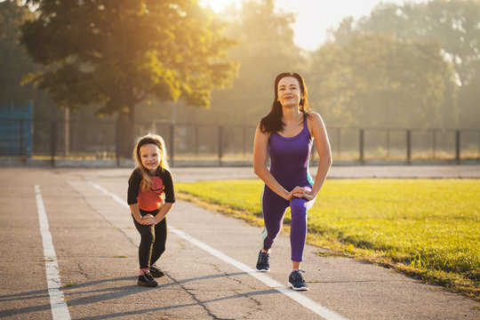 Mom and daughter on the morning sports training do a warm-up