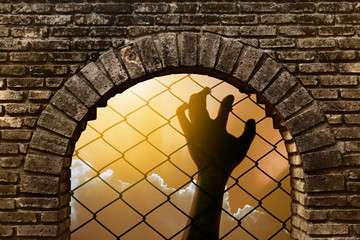 Silhouette of a hand catching metal fence the expression to be imprisoned in tunnel