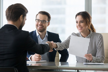Happy employers shake hand of male job candidate, congratulating with given position, satisfied HR managers happy to hire applicant handshake greeting at team. Successful good interview concept