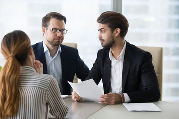 Dissatisfied male recruiters look at each other skeptic on female applicant candidature, disappointed HR managers exchange glances doubt in woman candidate. Bad interview, employment failure concept