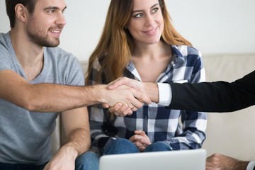 Happy millennial husband shaking hand of marriage consultant thanking for help, satisfied couple handshake relationships expert or psychologist greeting or welcoming. Family counselling concept