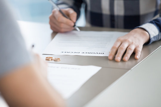 Close up of husband sign divorce decree ending relationships with wife, determined man put signature on document finalizing separation, breaking up or split officially. Marriage annulment concept