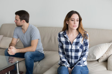 Offended husband and wife sit separately on couch avoid talking or looking at each other, millennial couple in fight ignore spouse, having disagreement or misunderstanding. Family problem concept