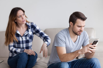 Mad wife shocked by indifferent husband behavior texting to someone, busy with smartphone, suspicious woman argue with beloved man distrusting him. Relationships, cheating problem concept