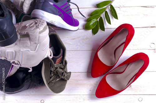 43644f037e3a Big heap of different sports shoes and red high heel women s shoes on white  background.