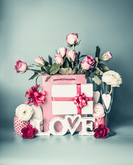 Festive composition with word LOVE greeting box with red ribbon, shopping bag with roses flowers, packing decorations, bottle of champagne, glasses and hearts , front view. Romantic concept