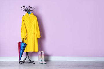 Wall Mural - Umbrella, raincoat and gumboots near color wall with space for design